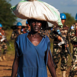 A displaced woman carries goods as United Nations Mission in South Sudan peacekeepers patrol outside the premises of the UN Protection of Civilians site in Juba on October 4, 2016.