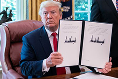 President Trump holding up document with signature on Executive Order on Iran sanctions
