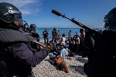 Weaponized migration image showing armed police and refugees