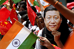Indian schoolgirl wears a face mask of Chinese President Xi Jinping