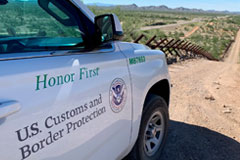 The passenger side door of a US Customs and Border Protection vehicle in the dessert