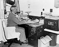 President Harry Truman reading reports of dropping the first atomic bomb