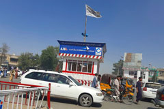 A Taliban flag flies in the main square of Kunduz, Afghanistan, after fighting between Taliban and Afghan security forces on Aug. 8. (Abdullah Sahil/AP)