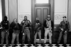 Members of a militia group outside the office of Michigan governor Gretchen Whitmer during a protest against her Covid stay-at-home order, Lansing, April 30, 2020. Three of them were later charged with being involved in a plot to kidnap her, attack the state capitol building, and incite violence.