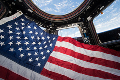On the International Space Station June 14, 2015 the crew of Expedition 44 prepare to observe Flag Day in the USA in the Cupola, the 360 degree observation point.