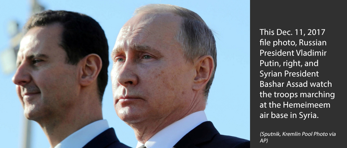 This Dec. 11, 2017 file photo, Russian President Vladimir Putin, right, and Syrian President Bashar Assad watch the troops marching at the Hemeimeem air base in Syria.