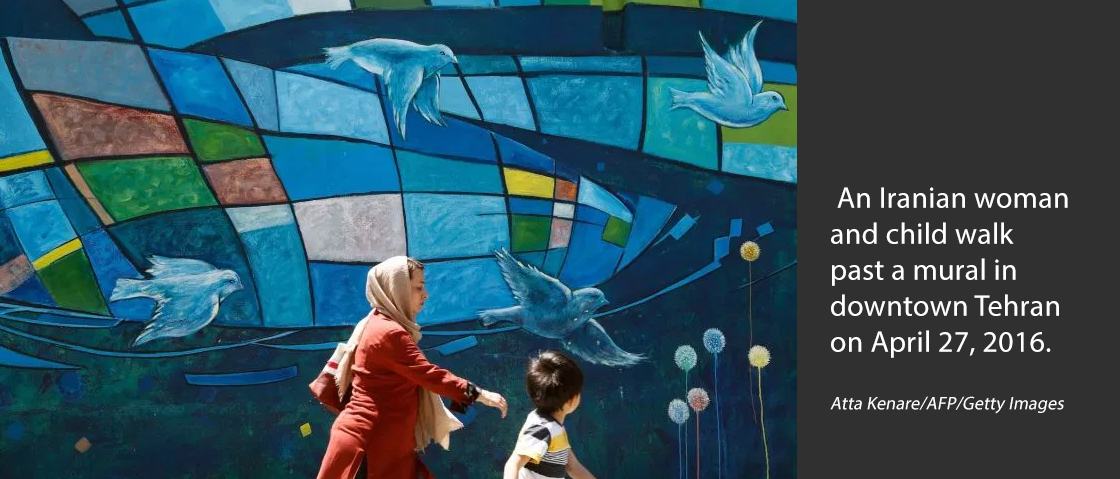 An Iranian woman and child walk past a mural in downtown Tehran on April 27, 2016. Atta Kenare/AFP/Getty Images