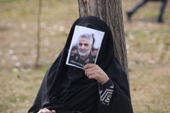 An Iranian woman covers her face with a picture of Iranian Maj. Gen. Qassem Soleimani during a demonstration in Tehran against the killing of the top commander in a U.S. strike in Baghdad. (Atta Kenare/AFP/Getty Images)