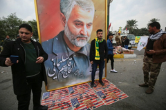 Posing for a picture with a poster of Maj Gen Qassim Suleimani in Baghdad on Saturday.Credit...Ahmad Al-Rubaye/Agence France-Presse — Getty Images