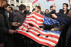 Iranians tear up a US flag during a demonstration in Tehran on January 3, 2020.
