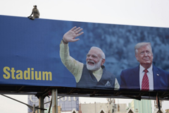 A monkey sits atop a billboard that shows India's Prime Minister Narenda Modi welcoming President Trump ahead of his visit to Ahmedabad, India, on Monday. (Ajit Solanki / Associated Press)