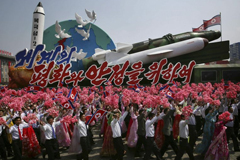 "North Koreans parade in Pyongyang in 2017 alongside a float with model missiles and rockets and the message, ""For Peace and Stability in the World."" (Wong Maye-E / Associated Press)"