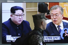 A TV screen at Seoul Railway Station shows file footage of North Korean leader Kim Jong Un, left, and South Korean President Moon Jae-in on Wednesday. (Ahn Young-Joon/AP)