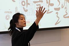 Woman in traditional Korean dress teaching Korean