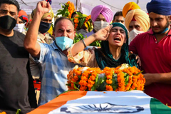 Sandeep Kaur and her brother Prabhjot Singh lay flowers on the coffin of their father, Satnam Singh, who was killed in the fight in the Galwan Valley. Photograph: Narinder Nanu/AFP/Getty Images