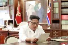 North Korean leader Kim Jong Un reads a letter from U.S. President Donald Trump in Pyongyang in this picture released Sunday. | REUTERS