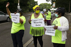 Annie Gordon, left, Gabrielle Rene, center, and Jenny Clark, right, rally for protection from evictions Saturday, June 27, 2020, in the Mattapan neighborhood of Boston. Massachusetts' tenant eviction moratorium is slated to expire in mid-August. (AP Photo/Michael Dwyer)