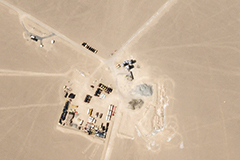 Chinese engineers erected an inflatable dome over the construction site of an underground missile silo, left, to hide the work below. Support facilities and temporary storage for construction equipment are seen at right.Credit...Planet Labs Inc.