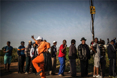 A municipal worker dances as voters line up in a township near Durban to cast their votes in South Africa's Aug. 3 elections.