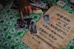 South Korean Lee Su-nam shows a selection of ageing family photos and his brother's high school diploma. Photograph: Benjamin Haas