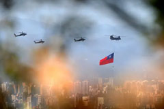 Military helicopters, one trailing a Taiwan flag, rehearse for Taiwanese national day celebrations. Photograph: Daniel Ceng Shou-Yi/ZUMA Press Wire/REX/Shutterstock
