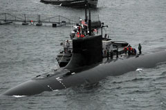 US Navy Submarine partially submerged under water, people walking on top of it