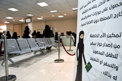 "Saudi women wait with their forms to apply for new passports on Aug. 29 at the Immigration and Passports Center in the capital, Riyadh, with a sign on the right reading out the details of a royal decree allowing women, age 21 and older, to obtain passports for themselves and for children in their custody, without seeking the approval of their ""guardians"" — fathers, husbands or other male relatives. (Fayez Nureldine/Afp Via Getty Images)"