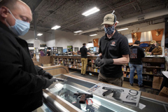 Cape Gun Works co-owner Toby Leary helped a customer in May. The demand for guns skyrocketed in 2020, with background checks jumping nearly 24 percent in Massachusetts.BARRY CHIN/GLOBE STAFF
