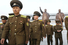 North Korean soldiers walk in front of bronze statues of North Korea's late founder Kim Il-sung and late leader Kim Jong-il at Mansudae in Pyongyang